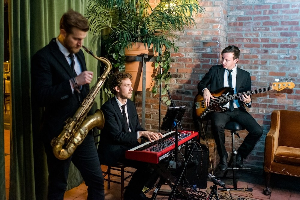 Cocktail hour jazz trio play saxophone, keyboard, and electric bass in a classy New York Hotel with exposed brick and green potted plant.