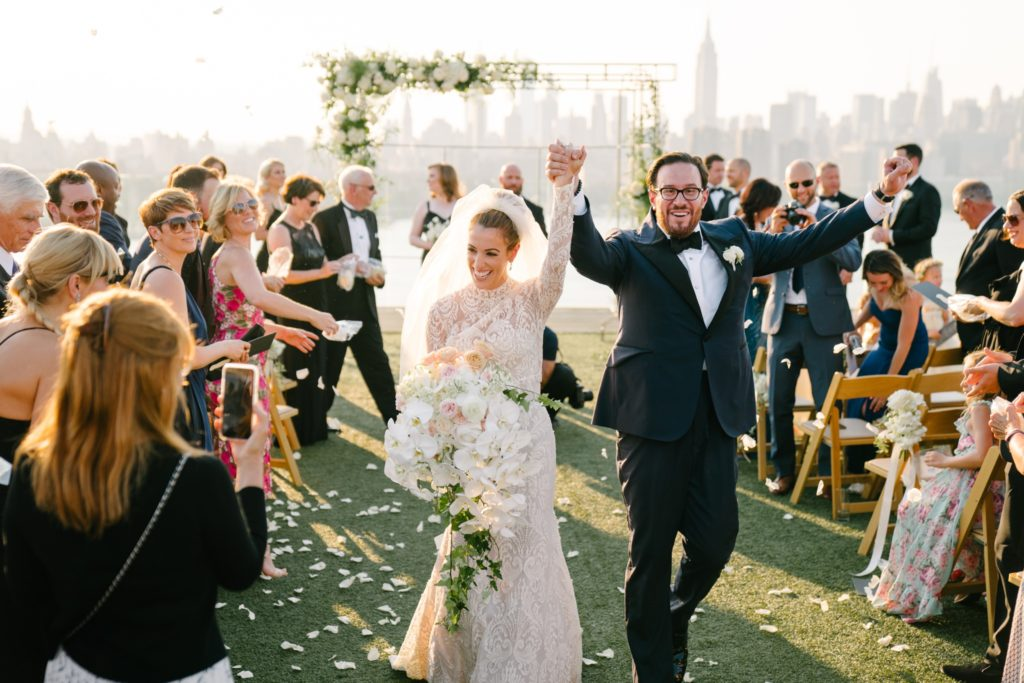 Guests throw rose petals atop a NYC rooftop as just married couple walks down the aisle hand in hand. Chic floral arch, elegant guests and Manhattan skyline in the background.